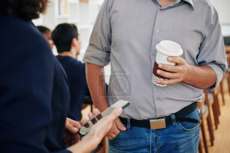Photo for Cropped image of businessman drinking take out coffee when talking to colleague during break - Royalty Free Image