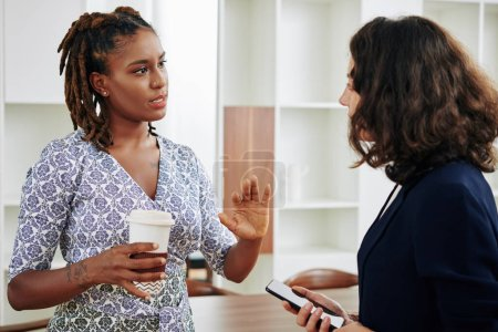 Photo for Serious young Hispanic businesswoman with cup of coffee in hand explaining her point to colleague - Royalty Free Image