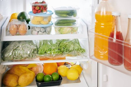 Photo for Full refrigerator after groceries delivery, citrus fruits, vegetables and greens on shelves - Royalty Free Image