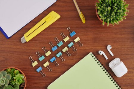 Photo for Paper clips and paper knife on wooden table of university student, view from above - Royalty Free Image