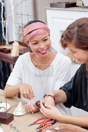 Photo pour Femme souriante appréciant faire des bijoux en studio avec ses amis - image libre de droit