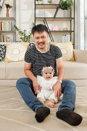 Photo for Young father enjoying spending time with his adorable little daughter at home - Royalty Free Image