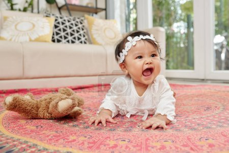 Photo for Little Asian baby girl enjoying crawling on the floor in spacious playroom - Royalty Free Image