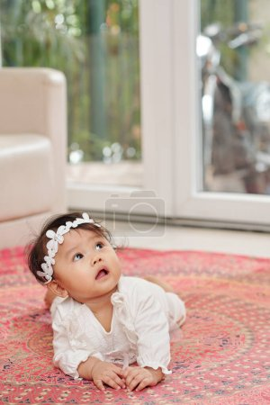 Photo for Curious little baby girl crawling on the floor at looking up at something interesting - Royalty Free Image