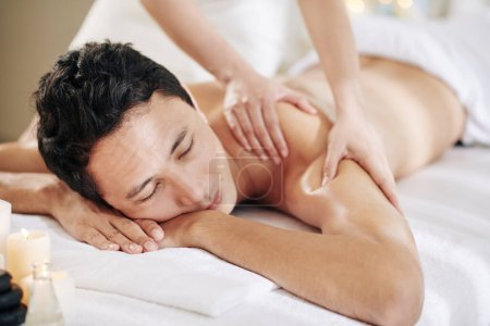 Photo pour Masseuse donnant massage profond du dos et des épaules des tissus au jeune homme - image libre de droit