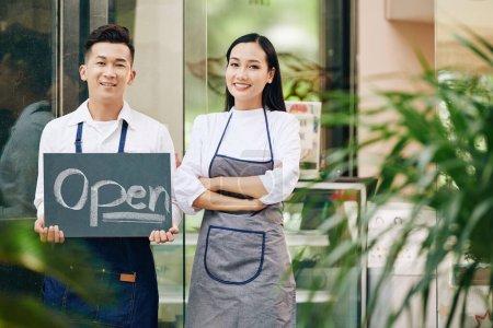 Photo pour Portrait de jeune serveuse et serveur confiant et heureux montrant signe ouvert et café d'ouverture - image libre de droit