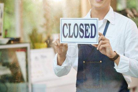 Photo pour Image recadrée du propriétaire du restaurant fermant la porte et accrochant signe - image libre de droit