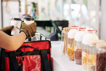 Photo pour Image recadrée de barista mettre des tasses avec chaud prendre le café dans un sac de livraison de nourriture isolé - image libre de droit