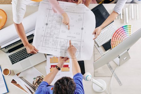 Photo for Group of architects pointing at blueprint of building, view from above - Royalty Free Image