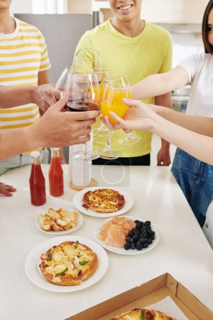 Photo pour Groupe d'invités de la fête de la maison cliquetis verres avec du jus de fruits sur la table avec de délicieuses collations et pizza - image libre de droit
