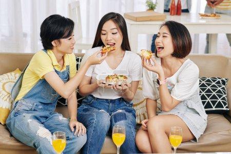 Photo pour Jolies jolies amies assis sur le canapé et mangeant de délicieuses pizzas à la fête de la maison - image libre de droit