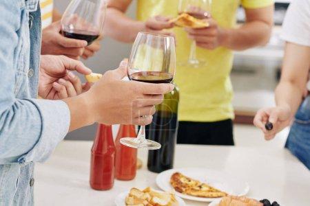 Photo pour Image recadrée d'amis buvant du vin rouge et mangeant de délicieuses pizzas à la fête de la maison - image libre de droit