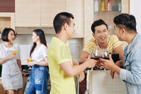 Photo pour Jeunes hommes buvant du vin et discutant des nouvelles et des commérages à la fête de la maison - image libre de droit