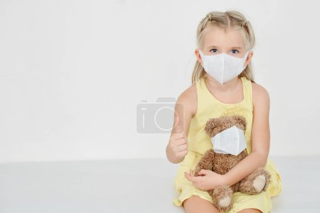 Photo for Little girl with medical mask on her face and face of her teddy bear showing thumbs-up - Royalty Free Image