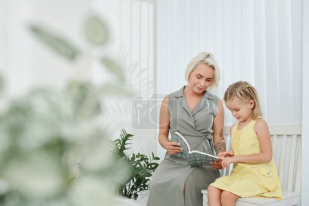 Photo for Smiling young mother showing interesting book to her little daughter - Royalty Free Image