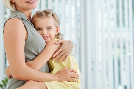 Photo for Cute little girl hugging her mother tight and looking at camera - Royalty Free Image