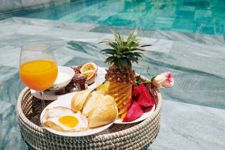 Photo for Breakfast consisting of fried egg, white bread and tasty sweet fruits on big wicker tray - Royalty Free Image