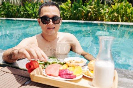 Photo pour Portrait de jeune homme en lunettes de soleil debout dans la piscine dans son jardin et manger un petit déjeuner sain et savoureux - image libre de droit