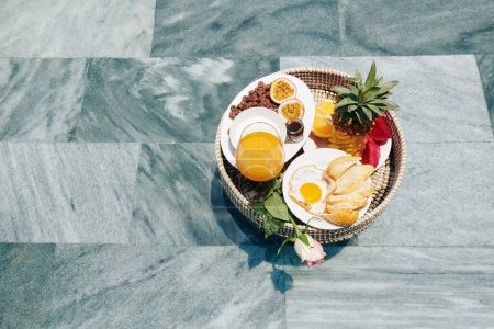 Photo for Wicker tray with delicious exotic fruits, fried egg with white bread and glass of juice served for breakfast - Royalty Free Image