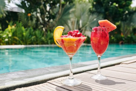 Photo for Two glasses with red dragon fruit and grapefruit smoothie on edge of swimming pool - Royalty Free Image