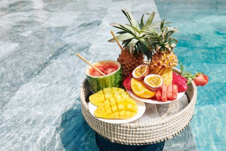 Photo for Various delicious exotic fruits on wicker tray floating in swimming pool - Royalty Free Image