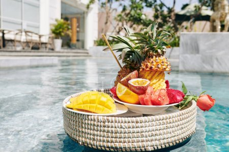 Photo for Plates with tasty sweet fruits on wicker tray floating in swimming pool of hotel - Royalty Free Image