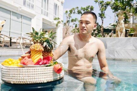 Photo pour Beau jeune vietnamien assis sur le bord de la piscine et mangeant des fruits mûrs savoureux - image libre de droit