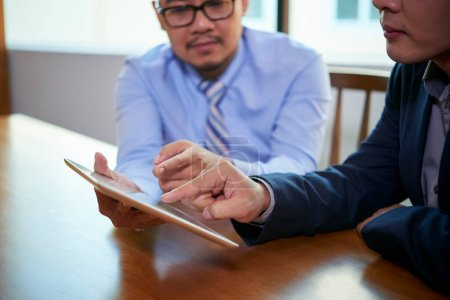 Photo for Two Asian male office workers sitting together at table using Internet on digital tablet, horizontal shot - Royalty Free Image