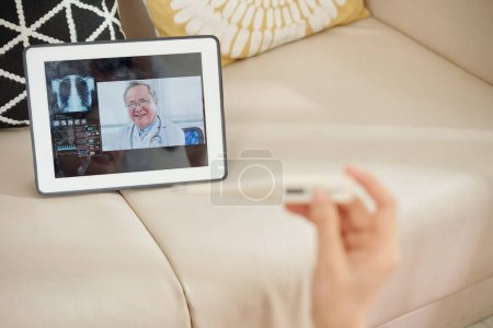 Photo for Woman with electronic thermometer in hand having telemedicine session with her doctor when staying home during quarantine - Royalty Free Image