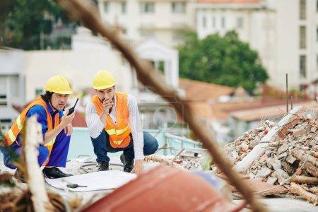 Photo pour Ingénieurs en gilets orange vif et hardhats discuter des travaux sur le chantier de construction - image libre de droit