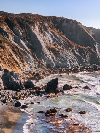 Photo for Scenic coastline along the Pacific Coast near Big Sur, California. Ocean waves crashing down on sharp rocks of Willow Creek Beach with steep cliff in the warm light of setting sun at the background. - Royalty Free Image