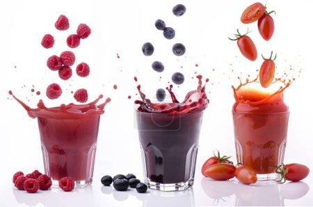 Photo pour Verres pleins de jus de tomate de bleuets et de framboises sur fond blanc - image libre de droit