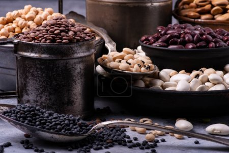 Photo for In different rustic metal bowls, on a gray textured background, variety of raw and colorful dry legumes rich in protein - Royalty Free Image