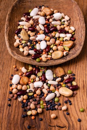 Photo for In the foreground, varieties of dried legumes mixed in a large spoon and on a rustic wooden background - Royalty Free Image
