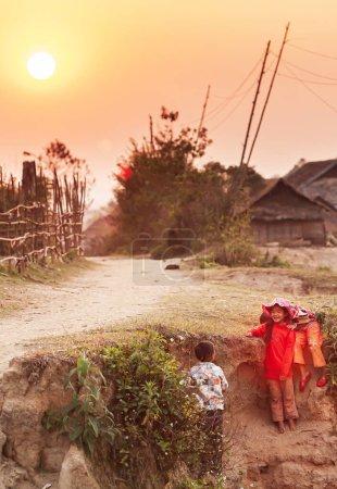 Photo pour Dien Bien, Vietnam - 26 FÉVRIER 2012 : Heureuses petites filles et garçons vietnamiens jouant sur le canal sec près du vieux village au coucher du soleil. Dien Bien Phu . - image libre de droit