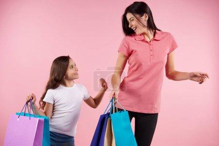 Photo pour Jolies maman et fille en vêtements décontractés avec des sacs en papier. Concept d'achats et de consumérisme. Isolé sur fond rose . - image libre de droit