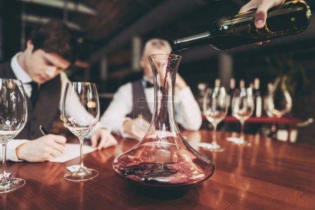 Nahaufnahme. Kellnerhand, die im Restaurant Rotwein aus Flasche in Karaffe gießt. Weinprobe.