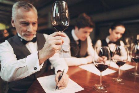 selbstbewusster Sommelier, der Wein im Restaurant verkostet. Verkostungsspezialist macht sich Notizen.