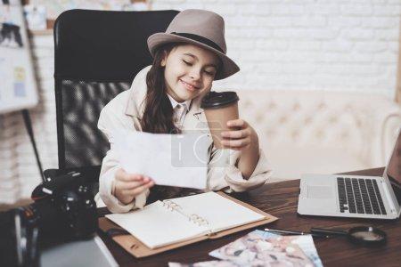 Photo pour Agence de détectives privés. Petite fille en manteau et chapeau est assis au bureau en regardant différentes photos et en buvant du café . - image libre de droit