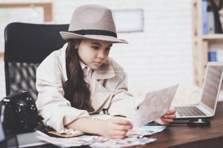 Photo pour Agence de détectives privés. Petite fille en manteau et chapeau est assis au bureau en regardant différentes photos . - image libre de droit