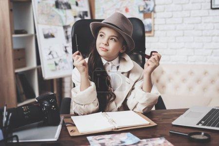 Photo pour Agence de détectives privés. Petite fille en manteau et chapeau est assis au bureau prenant des notes dans le carnet . - image libre de droit