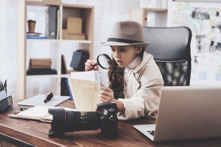 Photo pour Agence de détectives privés. Petite fille en manteau et chapeau est assis au bureau en regardant des photos avec loupe . - image libre de droit