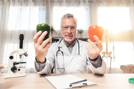 Photo for Doctor in white robe sitting at desk in office with microscope and stethoscope. Man is holding red and green peppers. - Royalty Free Image