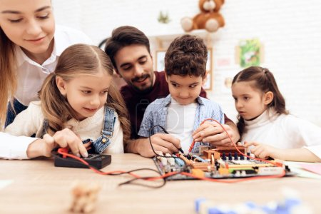 Photo for Children together with the teacher work with a soldering iron. They have a lesson. They learn to repair a computer part. - Royalty Free Image
