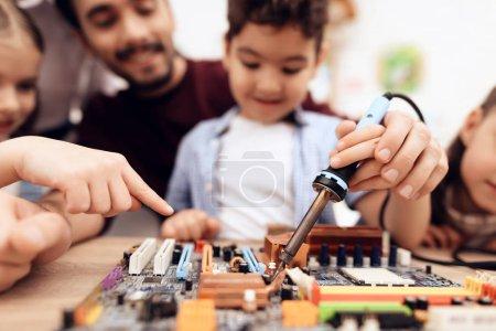 Photo pour Les enfants et le professeur travaillent avec un fer à souder. Ils ont une leçon. Ils apprennent à réparer une pièce d'ordinateur . - image libre de droit