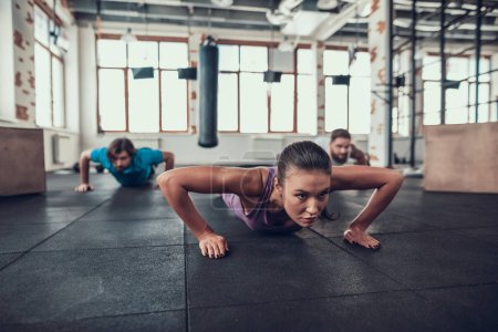 Photo for Men And Woman Doing Push Ups. Training Day. Fitness Club. Healthy Lifestyle. Powerful Athlete. Active Holidays. Crossfit Concept. Bright Gym. Comfortable Sportswear. Triceps Muscles. - Royalty Free Image