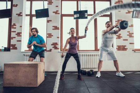 Photo for Jumps Rope Exercise And Weight Lifting. Training Day. Fitness Club. Healthy Lifestyle. Powerful Athlete. Active Holidays. Crossfit Concept. Comfortable Sportswear. Two Men And Girl. - Royalty Free Image