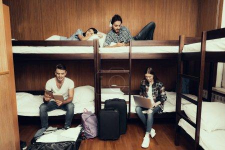 Photo pour Auberge pour les jeunes. Meilleurs amis voyageant. Petite chambre en auberge. passer du temps ensemble. lits superposés dans la chambre. Des gens souriants. Communiquez. s'asseoir et s'allonger sur le lit. Repose toi. travailler. lire. écouter de la musique - image libre de droit