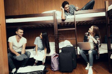 Photo pour Auberge pour les jeunes. Meilleurs amis voyageant. Petite chambre en auberge. passer du temps ensemble. lits superposés dans la chambre. Des gens souriants. Communiquez. s'asseoir et s'allonger sur le lit. déballer les bagages. les pouces levés - image libre de droit