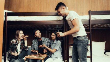 Photo pour Auberge pour les jeunes. Meilleurs amis voyageant. Petite chambre en auberge. passer du temps ensemble. Des gens souriants. amis assis sur le lit. Détends-toi. manger et boire. tenir les tranches de pizza. lits superposés dans la chambre - image libre de droit